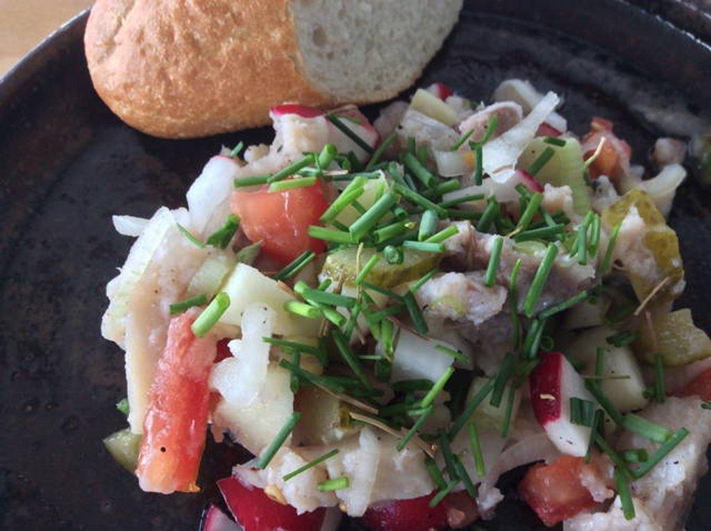 Matjessalat, auf Teller mit Schnittlauch