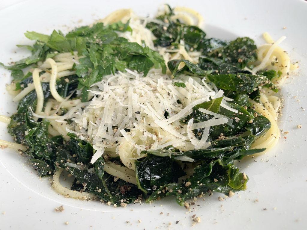 Bavette all aglio e olio mit Palmkohl anrichten
