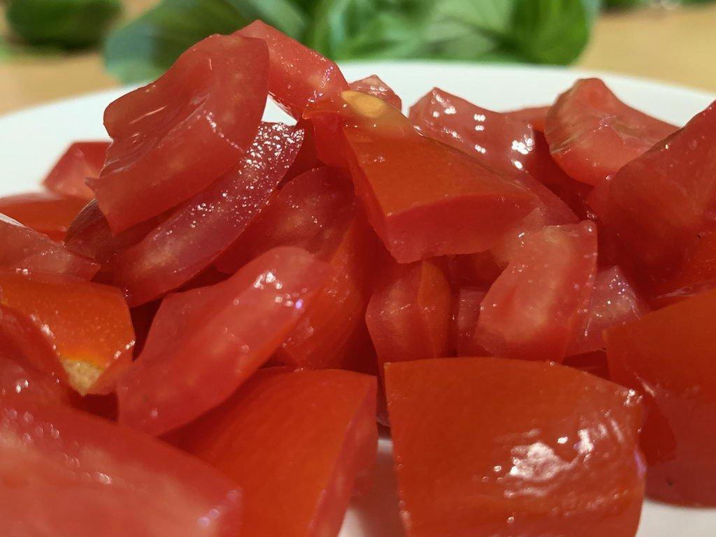 Ravioli mit Wurstfüllung an Basilikumbutter - entkernte Tomaten